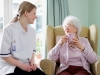 young nurse chatting with senior woman in care home